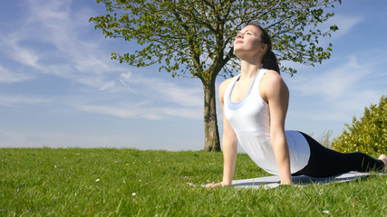 Young attractive woman doing yoga in beautiful natural surroundings