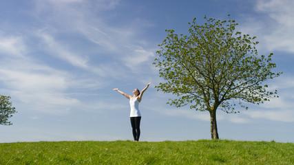 Young woman preforming sun salutation yoga move outside