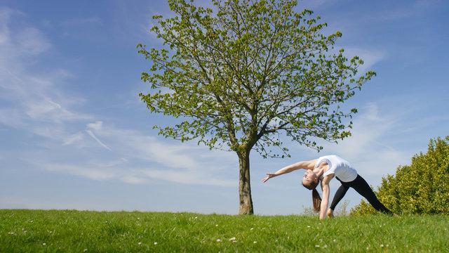 Young woman doing a yoga wild thing pose or Camatkarasana