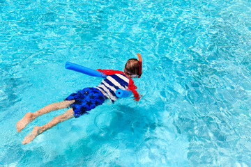 Little boy learns swimming alone with pool noodle