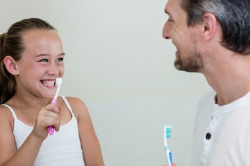 Smiling daughter and father holding a toothbrush in the bathroom