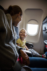 Mother and son talking and laughing on board of plane