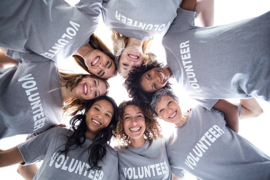 Happy multi-ethnic volunteers forming a huddle