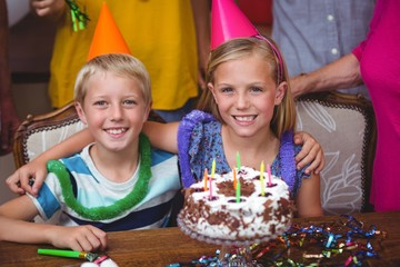 Smiling siblings with birthday cake