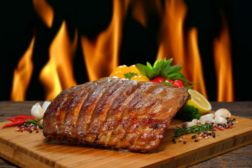 Fototapete - Grilled pork ribs and various vegetables on a chopping wood