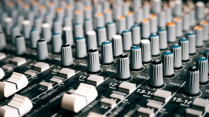 Mixing Board Sound Knobs. Pro audio mixing board faders and knobs, multi-track music recording equipment.