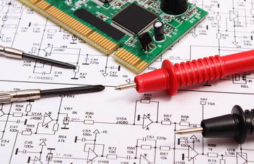 Printed circuit board. precision tools and cable of multimeter on diagram of electronics