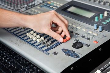 Professional's Hand Working On Audio Mixer In Studio
