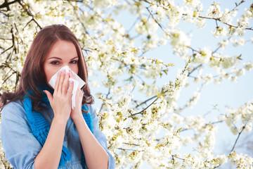 Junge Frau mit Taschentuch und Schnupfen vor Frühlingsblüten
