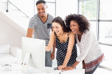 Businesspeople looking at computer and smiling