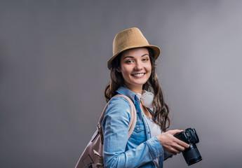 Tourist girl in denim shirt with camera, studio shot