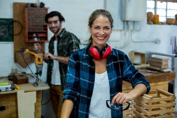 Male and female carpenter smiling in workshop