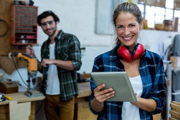 Portrait of female carpenter using digital tablet