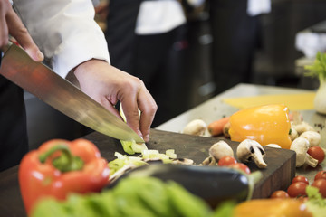 Professional cook chopping spring vegetables