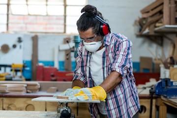 Carpenter working on wooden plank
