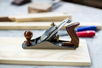 Wooden plank and jack plane on table