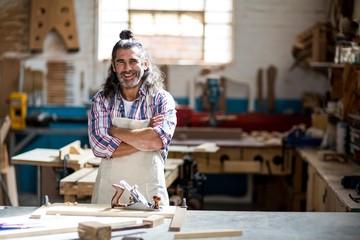 Portrait of smiling carpenter standing in workshop