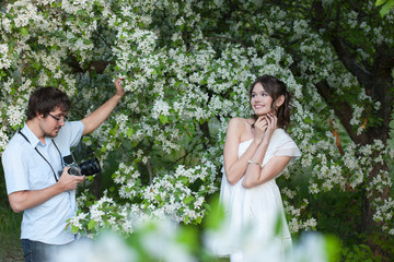 The man photographs the young girl in a garden/The man in a blue shirt photographs the young girl in a white dress under branches of a blossoming apple-tree