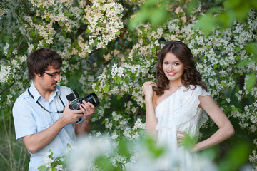 The man photographs the young girl in a garden