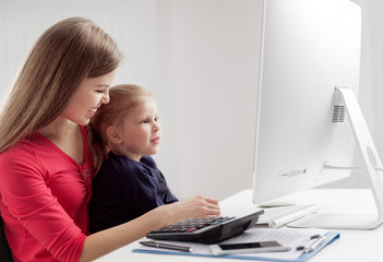 Smiling young mum holding her little cute daughter sitting at computer in home office. Family documents and budget concept.