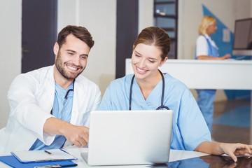 Happy doctors using laptop while discussing at desk