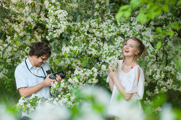 The man photographs the young girl in a garden