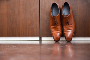 Brown leather shoes sitting on a wood floor