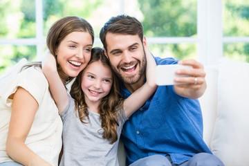 Laughing family clicking selfie with smartphone