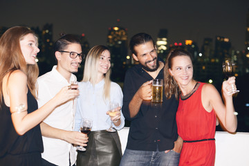 Happy people on rooftop party. Cityscape view at night.