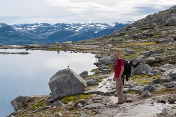 man walking on a mountain trail in Norway. Path to Trolltunga