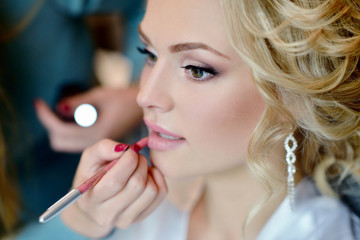 Wedding makeup artist making a make up for bride. Beautiful sexy model girl indoors. Beauty woman with curly hair. Female portrait. Bridal morning of a cute lady. Close-up hands near face Wall mural
