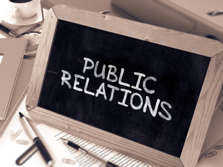 Public Relations Handwritten by White Chalk on a Blackboard. Composition with Small Chalkboard on Background of Working Table with Office Folders, Stationery, Reports. Blurred, Toned Image. 3D Render.