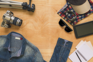 Top view of clothing and diverse personal accessory on wooden table background.