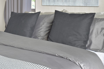 Black pillows on bed  in gray color scheme bedding