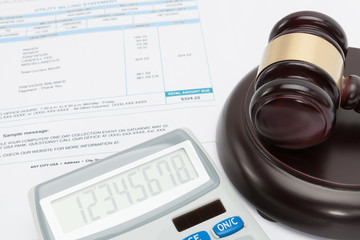 Unpaid bill with calculator and wooden gavel over it series