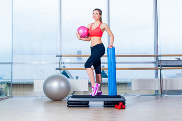 Fitness girl, wearing in sneakers, red top and black  breeches, posing on step board with ball, the sport equipment background,  gym