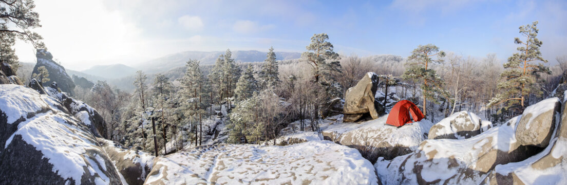 A red tent in snow standing on a rocky mountain summit in the cold winter sunny morning. Panorama image