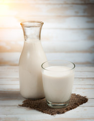 Milk in jar and glass on the old wooden,morning light