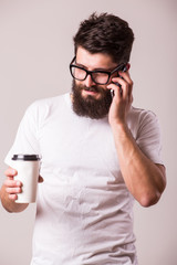 young man with coffee cup in hand and speak on phone while standing against grey background