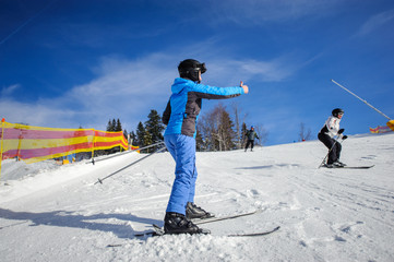 Rear view of female skier on a sunny day at ski resort on a ski slope giving the thumb up. Winter sports concept. Carpathian Mountains, Bukovel