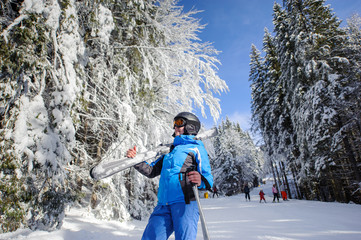 Portrait of active happy female skier on a ski slope in the winter forest on a sunny day. Woman is holding skis on her shoulder. Ski resort. Wide angle. Bukovel, Ukraine