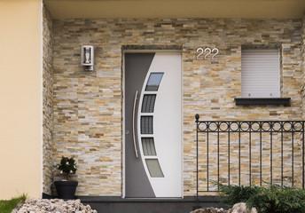 Moderner Eingang eines Hauses mit Haustür Fenster Geländer und Verblender aus Sandstein