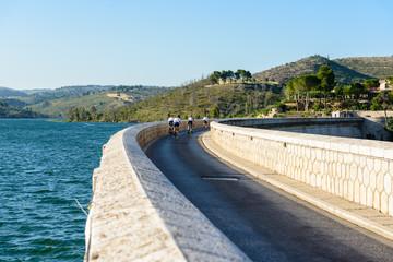 Cyclists crossing the Marathon dam