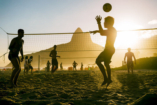 Silhouettes of Brazilians playing beach futevolei (footvolley), a sport combining football (soccer) and volleyball, at sunset on Ipanema Beach in Rio de Janeiro, Brazil