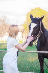 young woman petting a beautiful horse