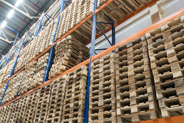 Huge distribution warehouse with wooden pallets on high shelves