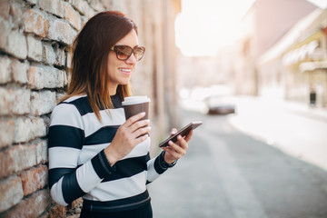 Young woman standing at the street drinking coffee to go and using mobile phone