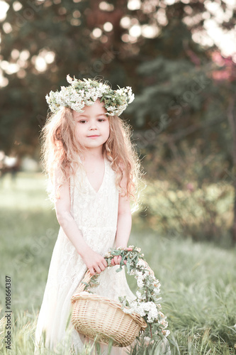 334eec0bc145 Beautiful baby girl 4-5 year old standing outdoors. Wearing stylish white  dress and floral wreath. Holding basket with flowers.