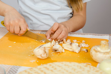 Close-up of childrens hands, cutting knife mushrooms on a cutting board
