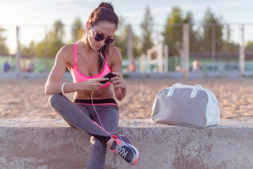 Athlete woman taking picture with smartphone camera, listining music, chatting on the beach summer holidays and vacation healthy lifestyle